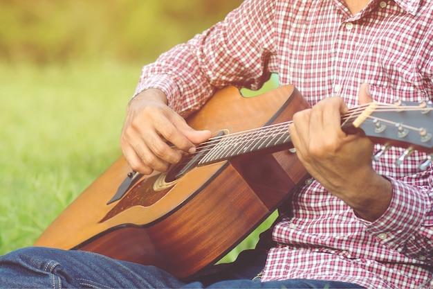 Stilvoller hipster-typ akustikgitarre spielen von hand. künstlermann musiker, der akustische gitarre im öffentlichen park spielt.