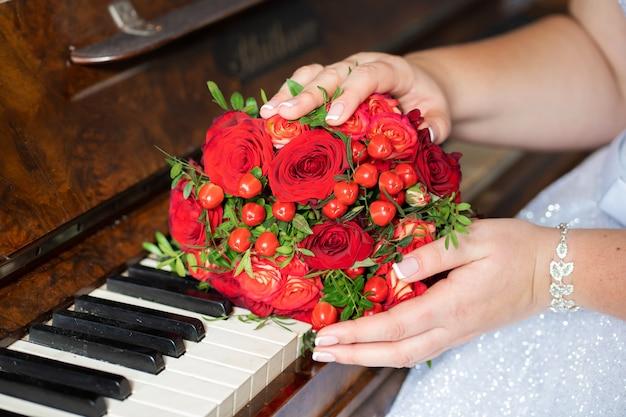 Stilvoller hochzeitsblumenstrauß von roten rosen auf dem klavier. hochzeitsdetails.