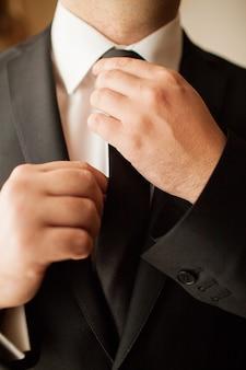 Stilvoller hochzeitsmorgen, der bräutigam in einem anzug kocht
