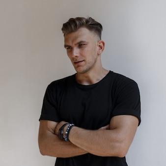 Stilvoller hübscher amerikanischer mann mit frisur im modischen schwarzen t-shirt, das nahe einer weißen wand aufwirft