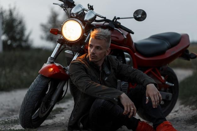 Stilvoller hübscher junger brutaler mann in einer modischen khakijacke sitzt nahe einem motorrad auf dem feld