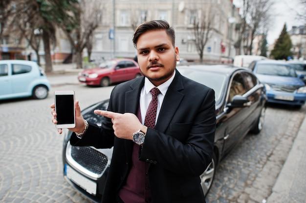Stilvoller indischer geschäftsmann in der formellen abnutzung, die gegen schwarzes geschäftsauto auf straße der stadt steht und finger zum handybildschirm zeigt.