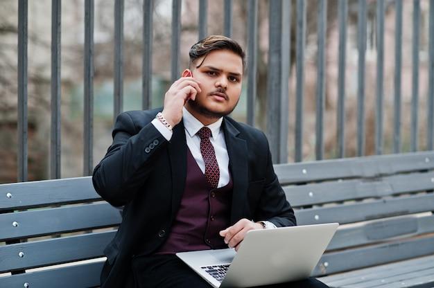 Stilvoller indischer geschäftsmann in der formellen kleidung, die auf bank mit laptop sitzt und auf handy spricht.