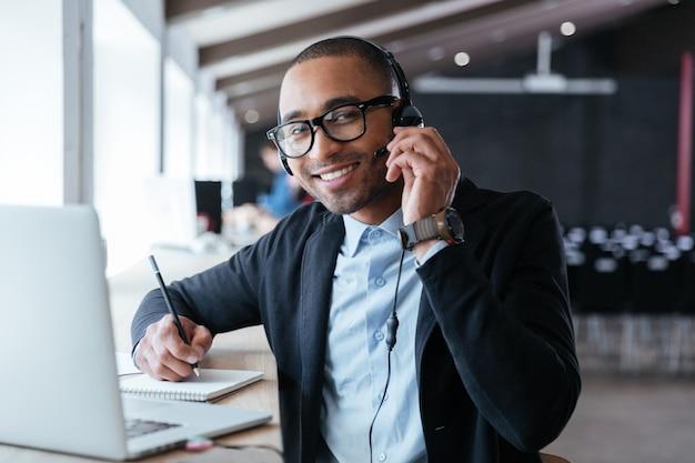 Stilvoller intelligenter geschäftsmann mit kopfhörern während seiner arbeit im büro headphones