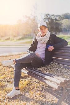 Stilvoller jugendlicher, der auf einer holzbank auf einer stadtstraße sitzt