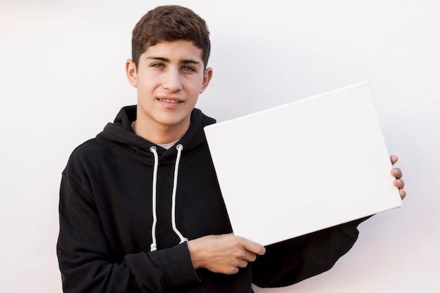 Stilvoller junge, der leeres weißes plakat gegen weiße wand hält