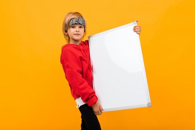 Stilvoller junge im roten kapuzenpulli und im weißen t-shirt hält zwei große blätter des papiers