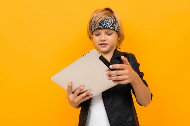 Stilvoller junge in der schwarzen jacke und im weißen t-shirt, die internet mit seinem tablett serfing