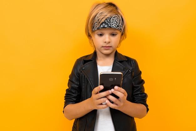 Stilvoller junge in der schwarzen jacke und im weißen t-shirt, die internet mit seinem telefon serfing