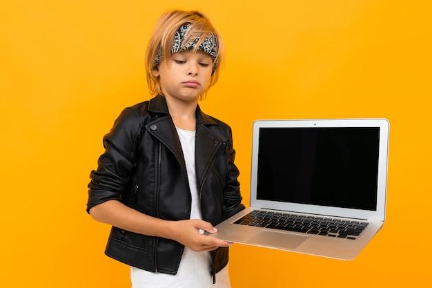 Stilvoller junge in der schwarzen jacke und im weißen t-shirt zeigt seinen laptop