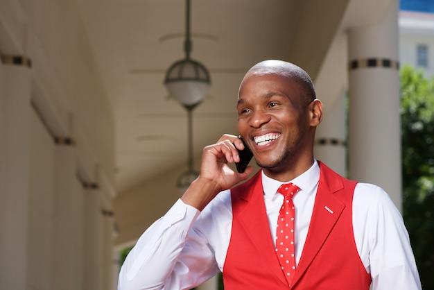 Stilvoller junger afrikanischer mann, der am handy spricht