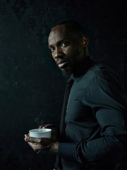 Stilvoller junger afrikanischer schwarzer mann mit weißer tasse kaffee, die auf dunklem studio aufwirft.