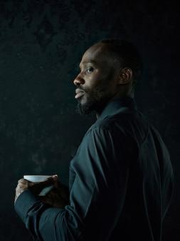 Stilvoller junger afrikanischer schwarzer mann mit weißer tasse kaffee, die auf dunklem studiohintergrund aufwirft.