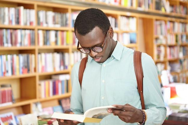 Stilvoller junger afroamerikaner-mann im hemd und in der brille, die durch buch im buchhandlungsstand schauen. schwarzer männlicher tourist, der lokale buchhandlungen während der reise ins ausland erkundet