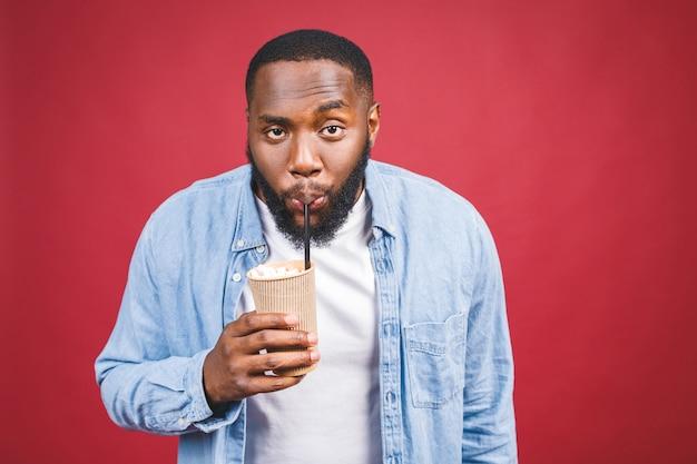 Stilvoller junger afroamerikanermann, der tasse des weggenommenen kaffees lokalisiert über rotem hintergrund hält.