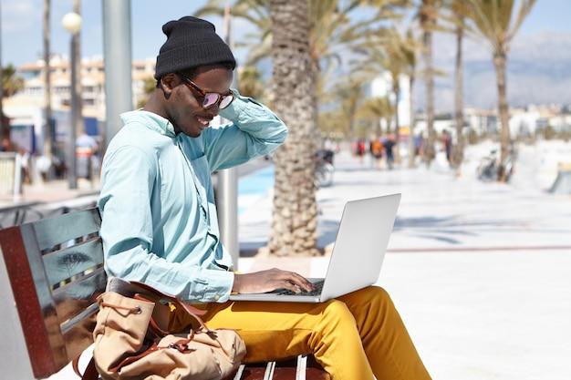 Stilvoller junger afroamerikanischer männlicher freiberufler, der hut und sonnenbrille unter verwendung des laptops für fernarbeit trägt, freie stadt-drahtlose internetverbindung benutzt und allein auf bank auf promenade am meer sitzt