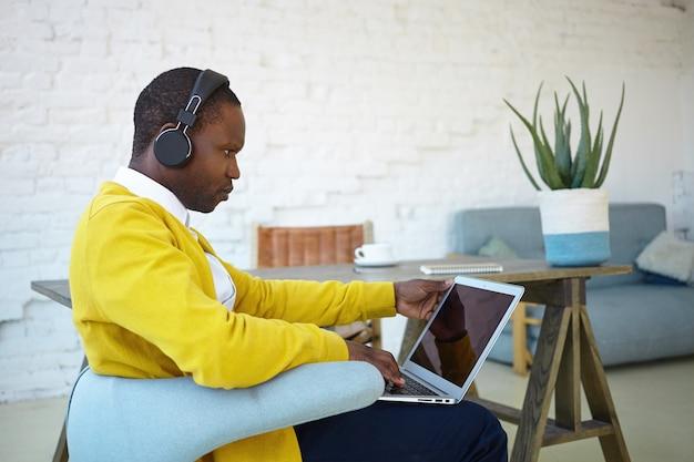 Stilvoller junger afroamerikanischer mann, der im stuhl zu hause sitzt, multitasking, mit laptop und kopfhörern, ernsthaften gesichtsausdruck habend. menschen, technologie, kommunikation und moderner lebensstil