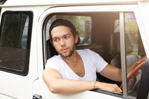 Stilvoller junger bärtiger hipster in t-shirt und hysterese, der über seinen weißen jeep zieht, nachdem er von der polizei auf der landstraße angehalten wurde. hübscher mann, der roadtrip genießt