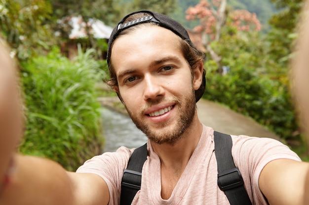 Stilvoller junger bärtiger männlicher blogger mit rucksack, der im freien aufwirft, während video aufzeichnet oder selfie nimmt