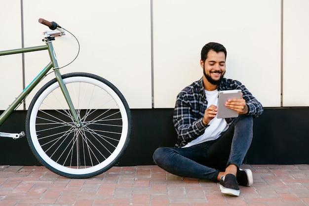 Stilvoller junger bärtiger mann, der eine tablette, nett lächelnd verwendet, etwas aufpasst oder liest