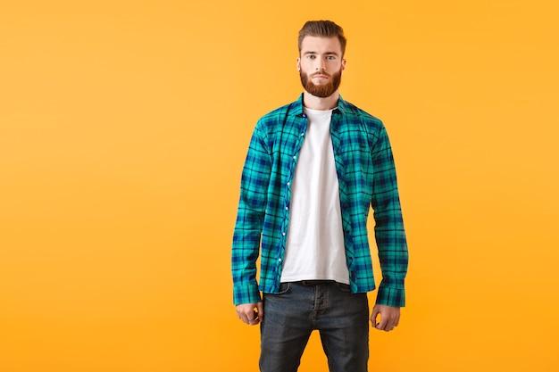 Stilvoller junger bärtiger mann im karierten hemd, das auf gelbe wandmode-trendartkleidung aufwirft