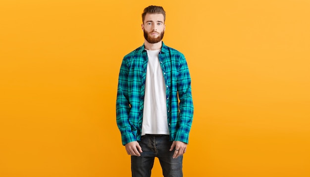 Stilvoller junger bärtiger mann im karierten hemd, das auf modetrendartbekleidung des gelben hintergrunds aufwirft