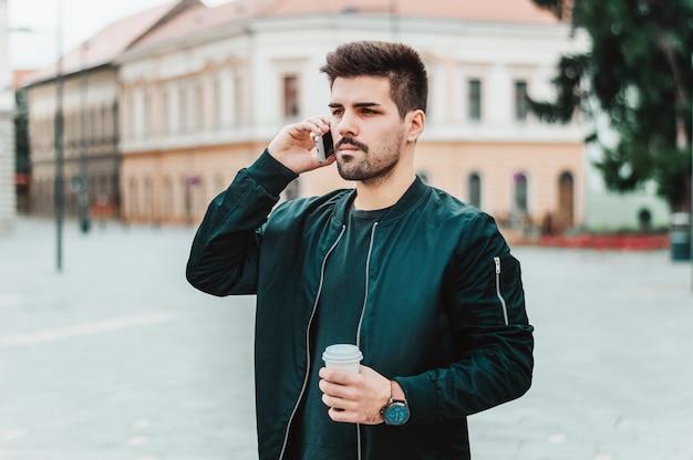 Stilvoller junger bärtiger mann in der zufälligen ausstattung spricht an seinem telefon draußen.