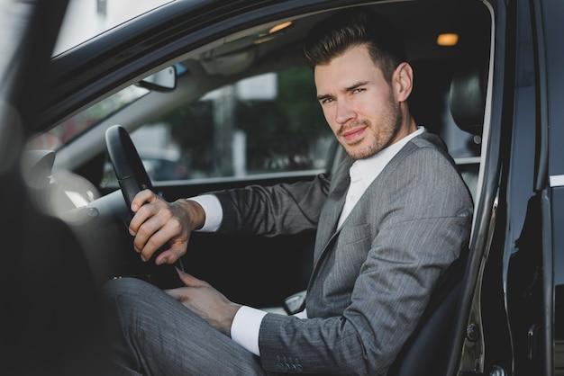 Stilvoller junger geschäftsmann, der im auto mit einer offenen tür sitzt