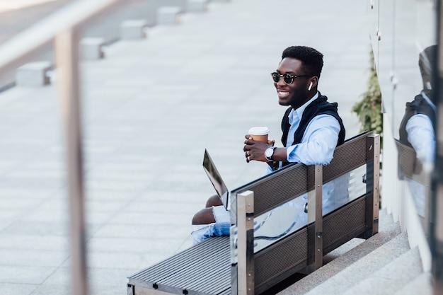 Stilvoller junger geschäftsmann, der mit seinem laptop auf einer sonnigen straße neben einem park auf einer bank sitzt. mit tasse kaffee. lebensstil.