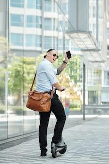 Stilvoller junger geschäftsmann in der sonnenbrille, die auf roller steht und freund über die straße winkt