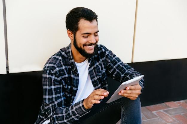 Stilvoller junger hippie-mann, der eine digitale tablette, nett lächelnd verwendet und betrachtet tablettenschirm