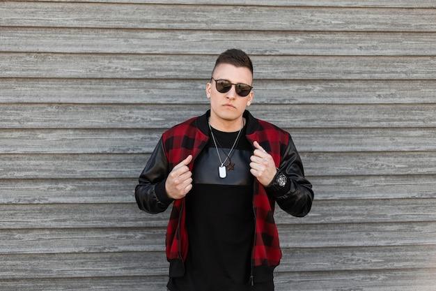 Stilvoller junger hipster-mann in der schwarzen sonnenbrille in einer modischen rot karierten jacke in einem trendigen schwarzen t-shirt mit amuletten um den hals nahe einer holzwand an einem sommertag