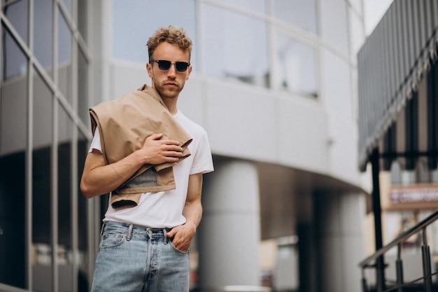 Stilvoller junger hübscher mann draußen in der stadt