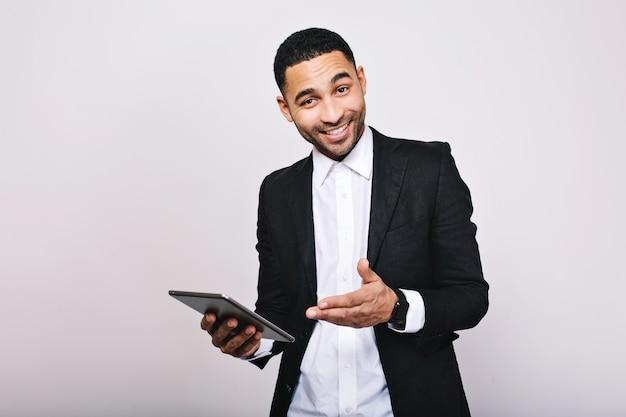Stilvoller junger hübscher mann im weißen hemd, schwarze jacke, mit tablett lächelnd. erfolg erzielen, großartige arbeit leisten, echte positive emotionen ausdrücken, geschäftsmann, kluger arbeiter.