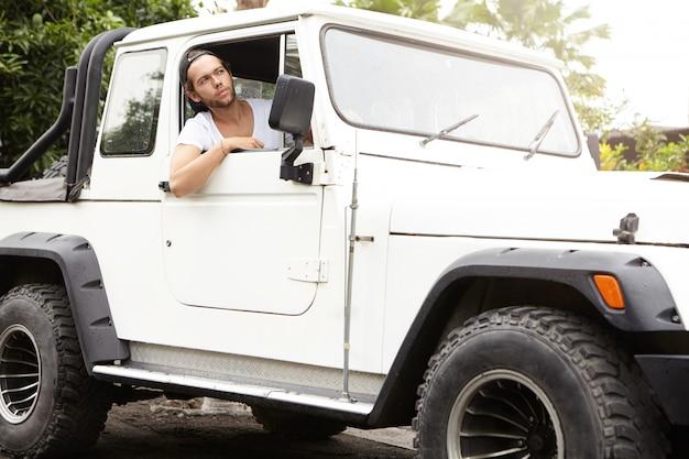 Stilvoller junger kaukasischer mann, der offenes fenster seines weißen sport utility vehicle schaut. unrasierter mann mit baseballkappe, der seinen jeep rückwärts fährt und den roadtrip genießt