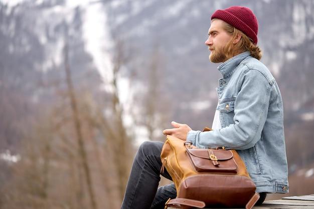 Stilvoller junger kaukasischer mann sitzt und erholt sich in der berglandschaft. tourist männlich