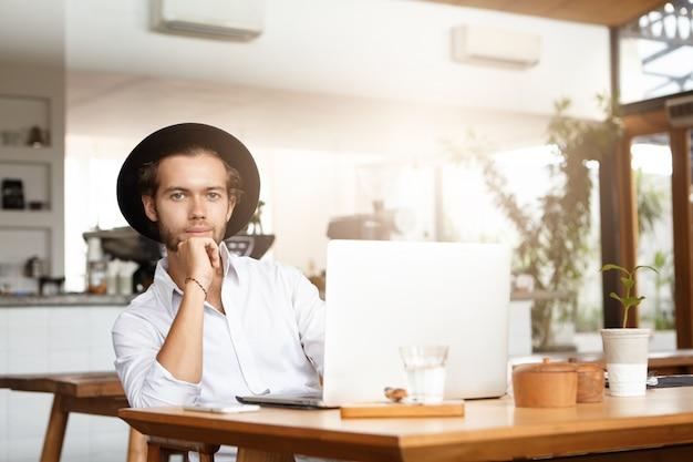Stilvoller junger kaukasischer student im schwarzen hut, der ruhe während der arbeit am diplomprojekt hat, am kaffeetisch vor offenem laptop-computer sitzt, sich auf seinen ellbogen stützt und mit lächeln schaut