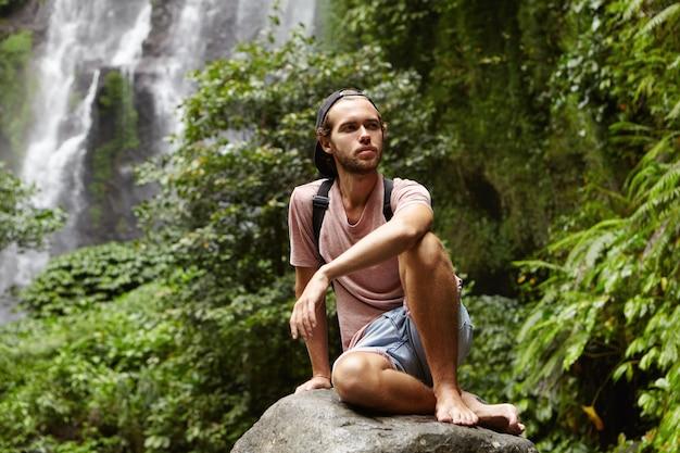 Stilvoller junger kaukasischer tourist mit rucksack, der barfuß auf großem stein mit herrlichem wasserfall hinter ihm entspannt. bärtiger rucksacktourist, der während der reise in den bergen auf felsen sitzt und müde aussieht
