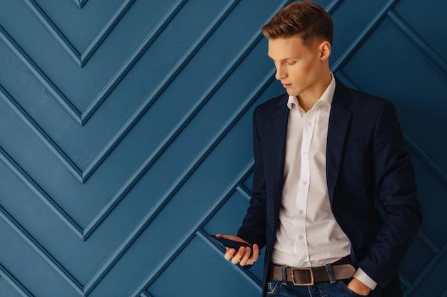 Stilvoller junger kerl mit einem telefon, junger geschäftsmann, freiberufler