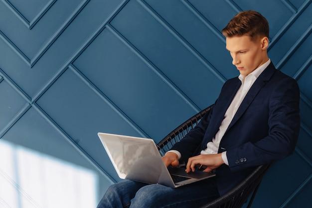 Stilvoller junger kerl mit laptop, junger geschäftsmann, freiberuflerarbeit, aquahintergrund