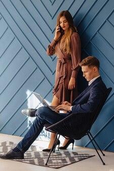 Stilvoller junger kerl mit laptop und mädchen mit telefon zusammen, junger geschäftsmann