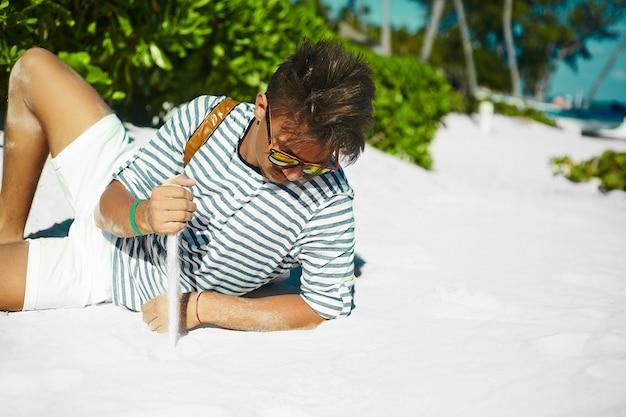Stilvoller junger männlicher vorbildlicher mann, der auf tragendem hippie-sommerhut des strandsandes liegt