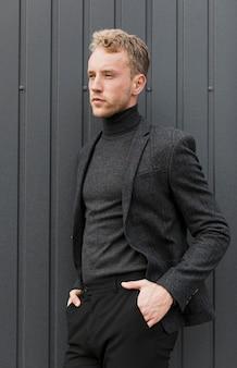 Stilvoller junger mann auf einem grauen hintergrund