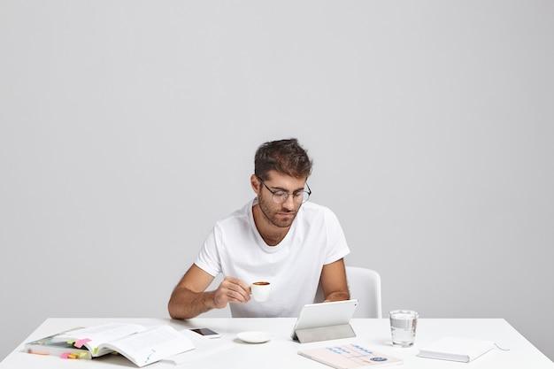 Stilvoller junger mann, der am schreibtisch sitzt