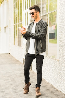 Stilvoller junger mann, der auf bürgersteig unter verwendung des smartphone steht