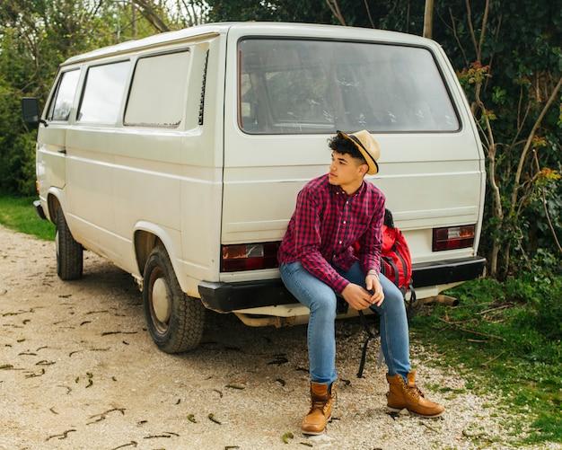 Stilvoller junger mann, der auf der rückseite des packwagens sitzt
