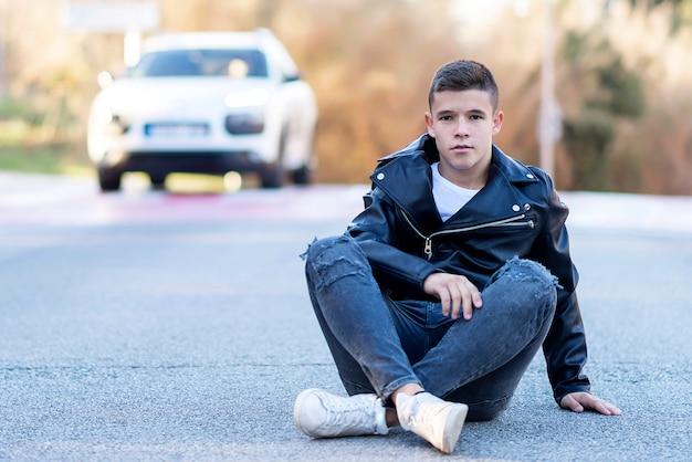 Stilvoller junger mann, der auf der straße sitzt, während kamera betrachtet