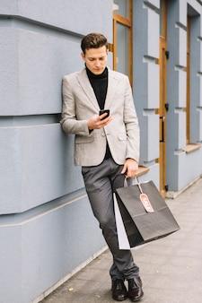 Stilvoller junger mann, der auf der wand betrachtet den smartphone hält einkaufstaschen sich lehnt