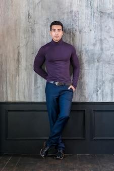 Stilvoller junger mann, der auf grauer wand mit seiner hand in der tasche sich lehnt