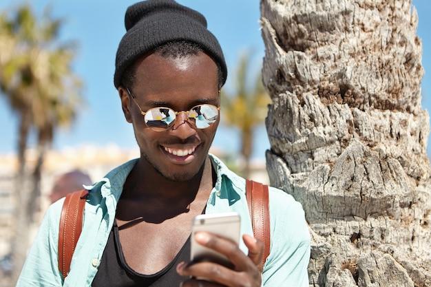 Stilvoller junger mann, der durch videos in den sozialen medien schaut